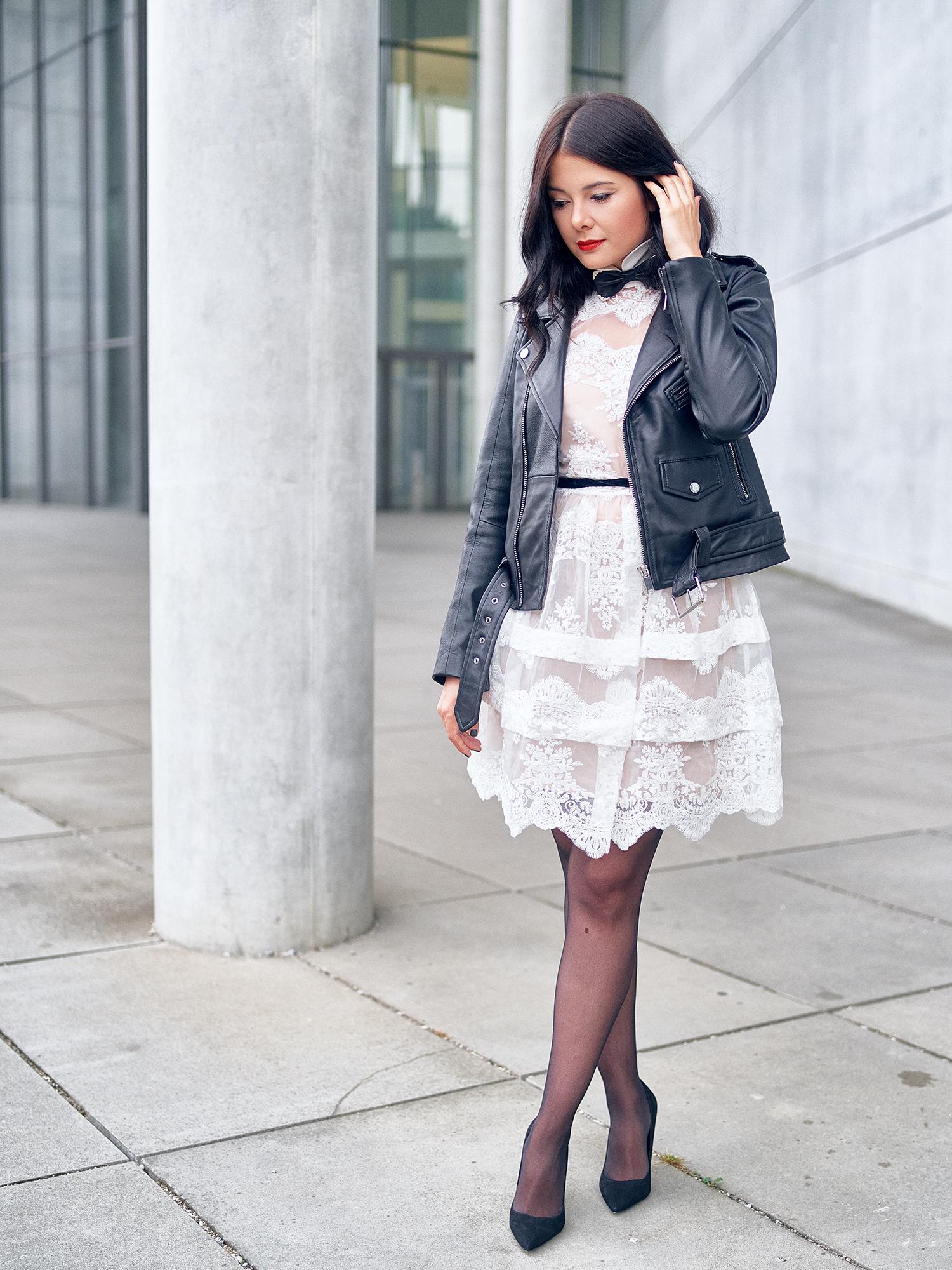 black and white lace dress weißes kleid mit Lederjacke und schwarzen Strümpfen und schwarzen Pumps sowie einer Fliege Fashionambit